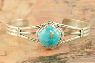 Genuine Castle Dome Turquoise set in Sterling Silver Bracelet. The Castle Dome Turquoise Mine is located about 30 miles from the Sleeping Beauty Mine, near Globe, Arizona. The Castle Dome Mine has not been in operation since the early 1970s. Created by Navajo Artist Milton Lee. Signed by the artist.